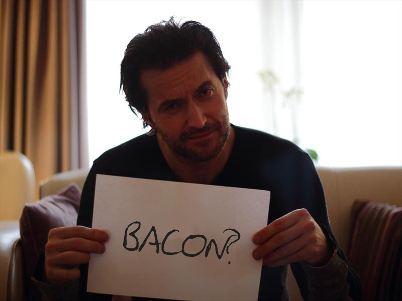 RA holding a sign saying 'Bacon?'